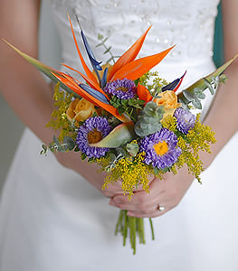 This unique combination of yellow roses, Birds of Paradise, and purple asters experiments with texture while exploding with color.