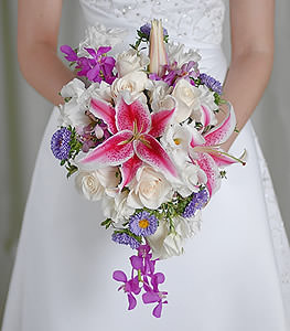 Traditional cream colored roses provide a delicate canvas allowing violet orchids, stargazer lilies and purple asters to paint a picture in eye catching hues.