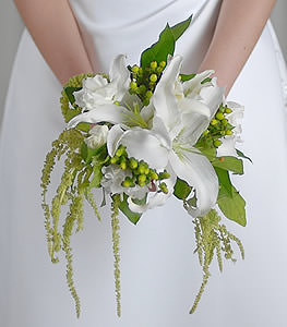 Although seeming rather unconventional, the clusters of green china berries deliver a breath of individuality while the delicate white lilies express a stunning lacy accent.