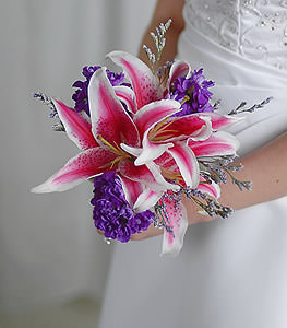 The attention grabbing color of the purple stock acts as the ideal accent to the dazzling stargazer lilies which steal the show in this dramatic, eye-catching arrangement.