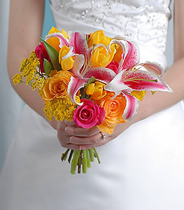 A bundle of bright and feminine flowers features yellow roses and tulips punctuated by the soft influence of pink roses and the eye-pleasing grace of stargazer lilies.