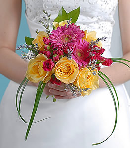 Festive and vibrant with a lovely mix of yellow and pink roses with gerbera daisies, this bouquet displays the joy and excitement of the special day to all who gaze upon it.