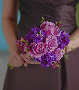 This monochromatic delight is achieved by placing together soft hued lavender roses with charming, more vibrant bundles of purple stock and waxflower.