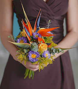 Fiery bursts of sunlight, birds of paradise add a modern edge to the colorful yet classic yellow roses and purple asters.