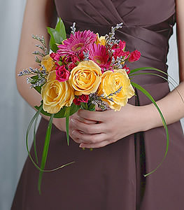 Warm yellow roses provide a stunning contrast to the hot pink gerbera daisies as hot pink mini roses blossom throughout the crevices.