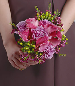 Bundles of green china berries and waxflower offer a gorgeous canvas for the hypnotizing hues of lavender roses and burgundy calla lilies to shine on.