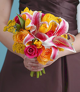 Mesmerizing hues of hot pink and yellow roses placed with vivacious stargazer lilies provide an eye catching arrangement.