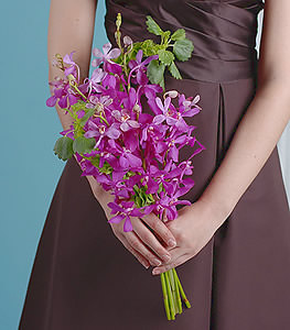 The deep green leaves of the bells of Ireland add depth while the mokara orchids radiate  bright hues of violet.