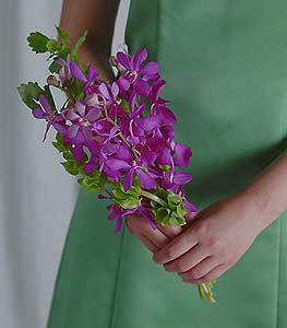 This simple and fragrant arrangement of violet mokara orchids and Bells of Ireland is a subtle touch.