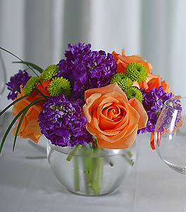 Fiery orange roses couple well with vibrant purple stock while incorporating texturally interesting green asters