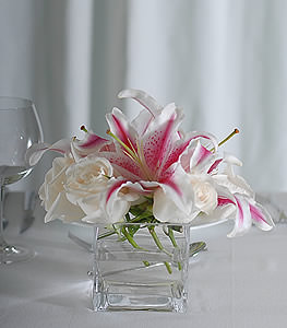 Adding a touch of drama to any table, stargazer lilies make a grand entrance as snow white roses provide an amazing follow up act.
