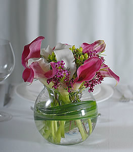 The adventurous pink and stargazer lilies form a unique envelope that encompasses the perky, green chinaberries and delicate waxflowers.