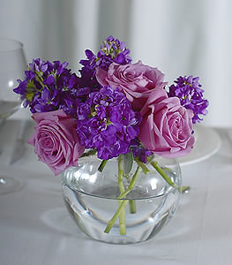 Gentle lavender roses support the upbeat personality of the purple stock, all the while stabilizing a soothing ambiance.