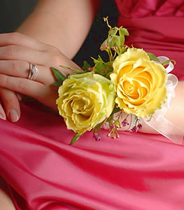 Conveying verdant warmth, this corsage pairs a bright yellow rose with a stylish jade rose, accenting the duo with berries and soft foliage.