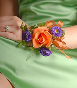 The vibrant warmth of an orange rose bloom is contrasted by dark purple matsumoto asters in this stylish corsage.