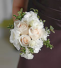 Keeping with tradition, classic cream roses and white lisianthus portray a refined elegance.
