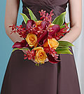 The striking combination of orange roses, burgundy mini calla lilies and red mokara orchids is regal in tone but modern in presentation.