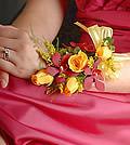 The bright, sunny charm of yellow spray roses provides a vivid partner to the deeply hued Mokara orchids.