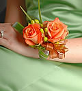 This vibrant corsage pairs vivid orange roses with green hypericum and folded lily grass.