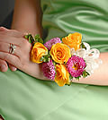 A study in contrast, this corsage pairs vivid yellow spray roses with bold hot pink Matsumoto asters.